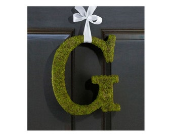 The letter in artificial green moss