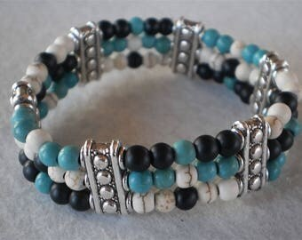 Stretch bracelet of semi-precious turquoise and glass beads with metal dividers.