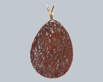 A dinosaur bone pendant by the late Howard Ball