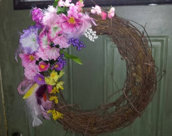 Beautiful grapevine wreath with flowers and feathers