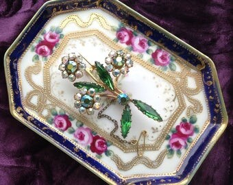 1940s gilt brooch with a spray of claw set aurora borealis clear glass, and green glass crystals