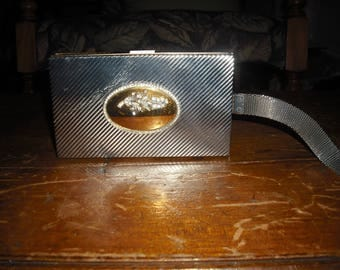 Silver wristlet compact is intracally desinged and has a several accesories
