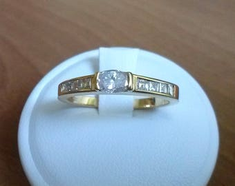 Gold ring with central cushion cut diamond and side square cut diamonds