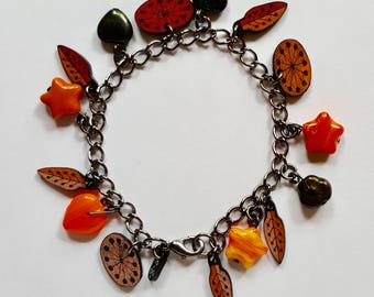 Orange charm bracelet with glass beads and shrink plastic charms
