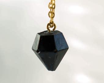 Gold necklace, diamond pendant, concrete