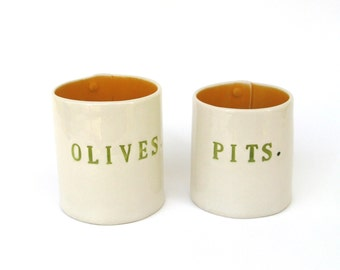 olives and pits  ...  hand built porcelain containers ...  bold yellow vessels