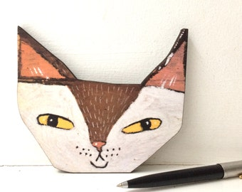 Laser cut print on wood of a pointy eared cat face
