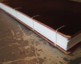 Coptic Binding - Handbound in raw natural leather, with decorative fabric paste-downs