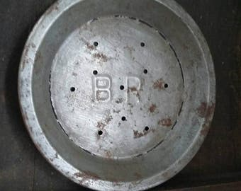 Vintage metal small pie plate with 10 holes embossed with B.R.