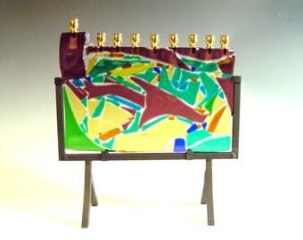 Fused glass Hanukkah menorah on iron pedestal. Hanukkiah glass with iron pedestal. Glass menorah with brass candle cups.