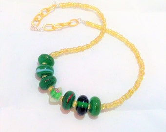 Golden seed bead and green lamp work beaded necklace with gold plated chain detail