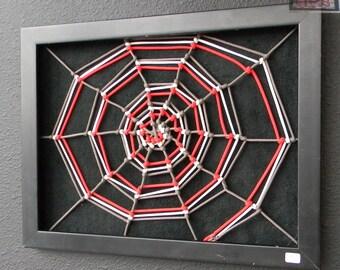 wood framed tri color spider web over black fabric