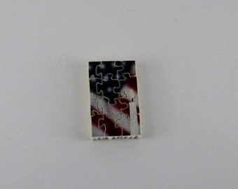 American Flag with candle in foreground stamp-sized puzzle