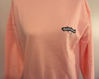 Peach womens sweater with motorhead logo and rosebud size medium