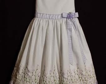 Adorable little girl white  of quality, with full skirt adorned with a lavendor check rebbon and flowers.