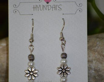 These dangle earring have a silver flower with white pearly beads