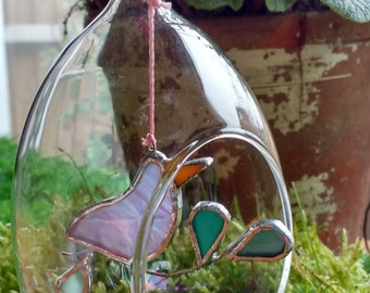 Easter decoration, coloured bird in blown glass egg.