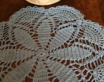 Crocheted doily in a pretty light blue color.
