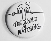 The World is Watching - political protest pin back button