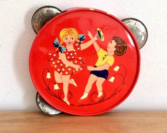 Mid-century bright red child's tambourine with a depiction of two children at play. Vintage tin-plate toy. Ancien jouet tôle : tambourin.