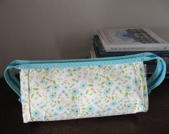 A super useful bag with so many zippers. Tiny blue and yellow floral pattern with three individual zippered pockets.  Blue full zipper.