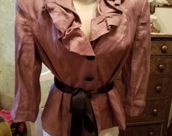Dusty pink blouse, big black buttons, and a black satin ribbon to tie at your waist. Fully lined  with a big ruffled neckline. Size eight.