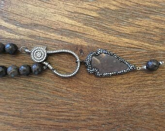 Necklace of brown jade beads finished with a jewel encrusted arrowhead pendant