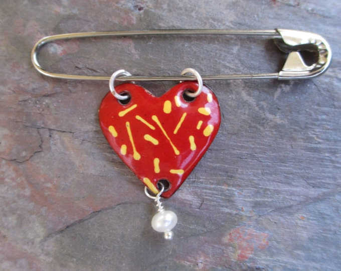 Red heart pin with yellow accents and a freshwater pearl hanging from a safety pin