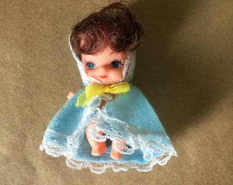 Tiny Plastic Doll Wearing Blue Cape Doll with Big Blue Eyes