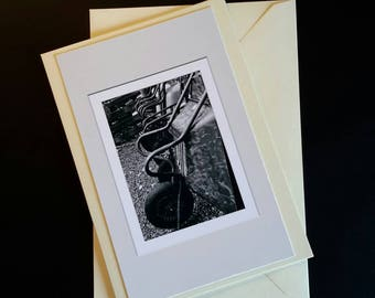 A photographic card of a row of wheel barrows.