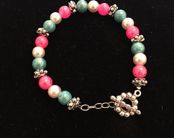 7.5 inch silver and pink, white, and blue pearl bracelet.