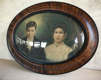 Antique bubble glass portrait of Spanish couple, convex oval frame, Victorian portrait, hand colored photograph in faux tiger wood frame