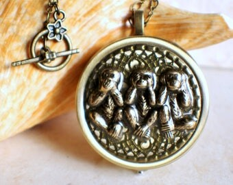 Monkey music box locket,round locket with music box inside, in bronze with monkeys.