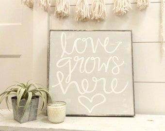 Love grows here grey and white rustic wood sign