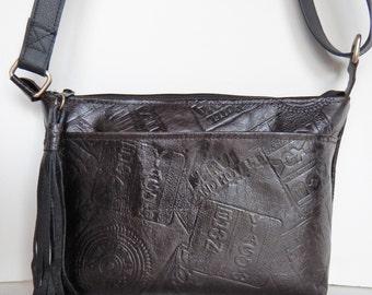 Dark brown leather crossbody or shoulder bag, with embossed travel tag design.