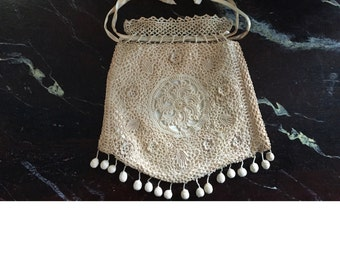 a wedding purse on silk crochet with pom pom appointments and silk satin interior,circa 1930