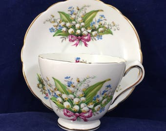 Regency, England, Bone China cup and Saucer.  Decorated with sprays of of snow drops tied with pink ribbons.  Both pieces edges in gold