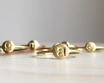Anelli sottilissimi con iniziale, cuore, stella o smile in oro 18k.  Anelli nascita sottilissimi in oro satinato o lucido.