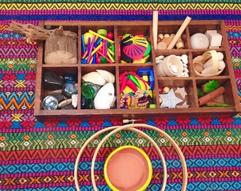 Multicultural loose parts tinker tray with ceramic bowl knitting hoop and brightly colored tapestry Reggio Emilio Waldorf Montessori open en
