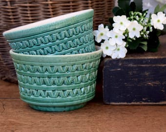 Handmade vintage pair of green textured ceramic bowls or dishes.