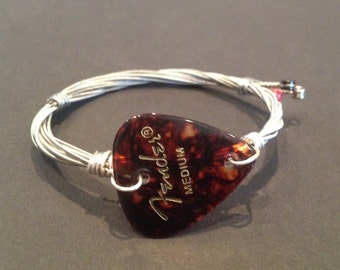 A handmade recycled guitar string bracelet/bangle with a fender plectrum.