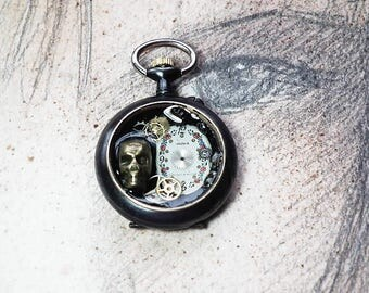 Little handmade unisex Steampunk-gothic pendant; black pocket watchcase,   skull , dial, gears in resin With  a black leather strap