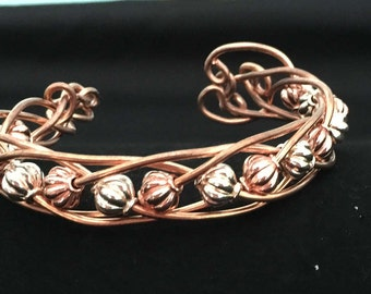 copper wire bracelet with bobbles weaved throughout the bracelet