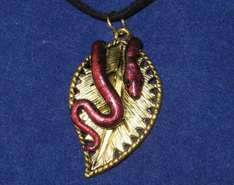 Black and red snake on a gold leaf pendant
