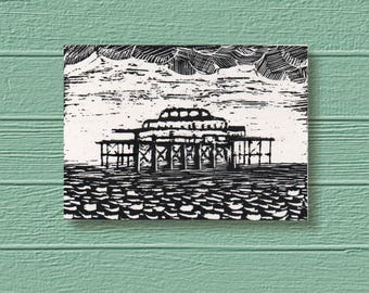 West Pier Brighton Original Art ACEO. Bold black & white design of old ironwork silhouetted against the sky, engraved on scratchboard.