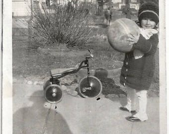 Old Photo Girl holding Ball wearing Knit Coat and Hat Tricycle on Sidewalk Shadow 1920s Photograph Snapshot vintage Child