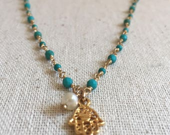 Turquoise gemstones and a freshwater pearl gold necklace with a hamsa charm