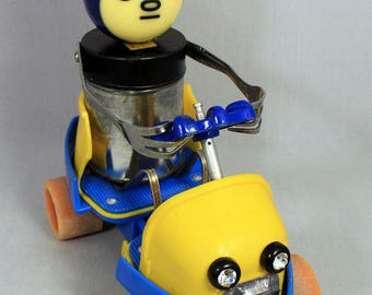Robot driver sculpture, auto related, whimsical, found object art . Up cycled from re-purposed materials. ~ Tenny in his F.P. Roadster.