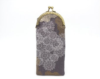 Glasses case made of taupe cotton with brown and white motifs, closed with a bronze metal clasp