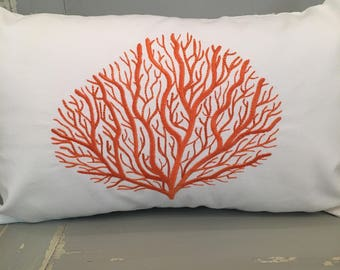 Coral embroidered pillow on white fabric